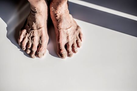 The image of the feet of an elderly old person that is worn down