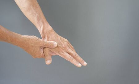 Hands and bones, joints of the fingers with the problems of the elderly on a gray background with free space