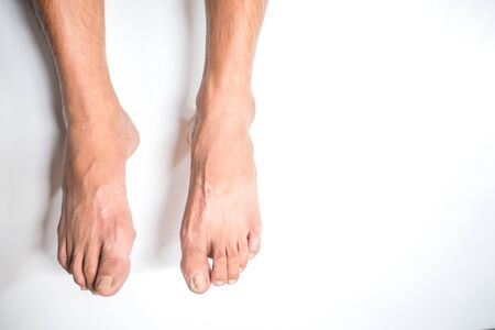 Man's feet hanging on the white background Stock Photo