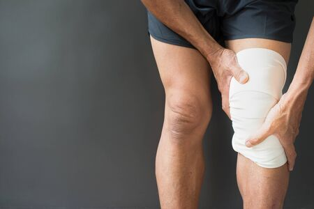 The image of the person holding the muscles around the knee with a bandage On a gray background with free space