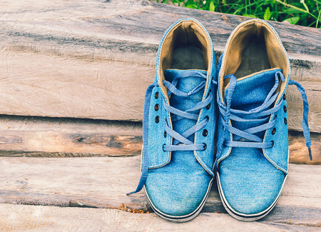 Old blue sneakers on wooden