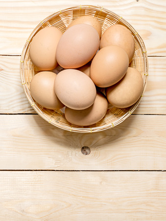 Hen eggs in basket on table wood top view for background