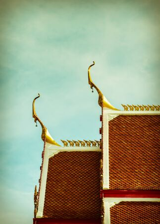 Roof Buddhist temple on sky background in Thailand, Retro style. Banco de Imagens
