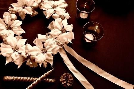 白いポインセチアのクリスマスの花輪および蝋燭