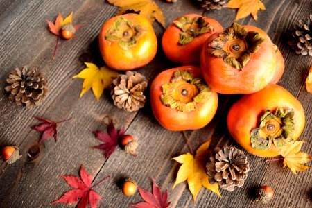 Persimmons with autumn maple leaves photo