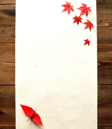 Red autumn maple leaves with origami crane photo