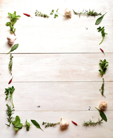 Green herbs with garlic frame white wood background Stock Photo