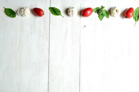 白いウッドの背景にトマト、ニンニク、バジルの葉 写真素材
