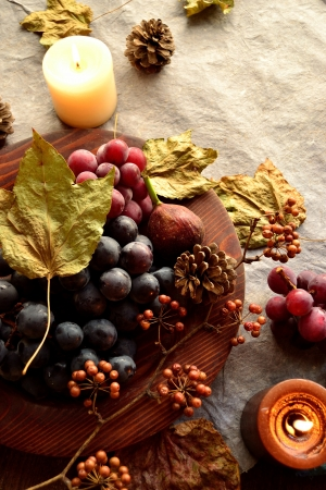 Grapes,candles and fall leaf paper background