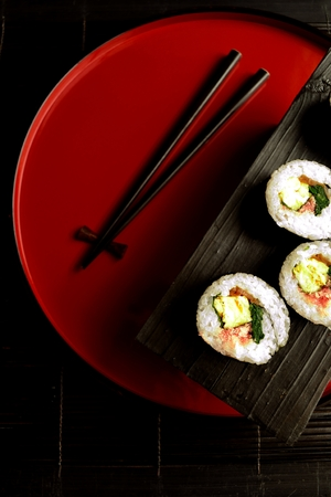 lacquer ware: Sushi roll  with chopsticks on Japanese red tray  Stock Photo