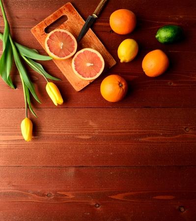 감귤류의 과일: Colorful citrus fruits with yellow tulips 스톡 사진