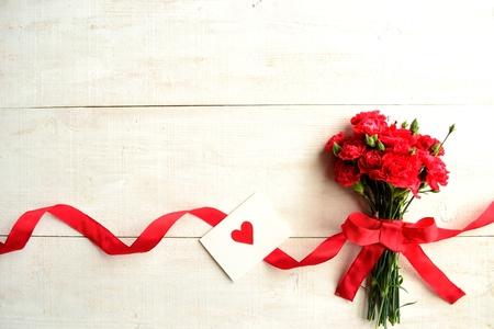 メッセージ カードが付いている赤いカーネーション花束