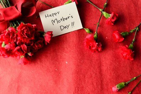Mothers day message card and red carnations bouquet Stock Photo