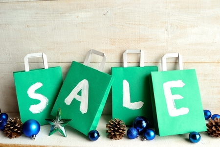 Green bargain sale shopping bags with Christmas ornaments