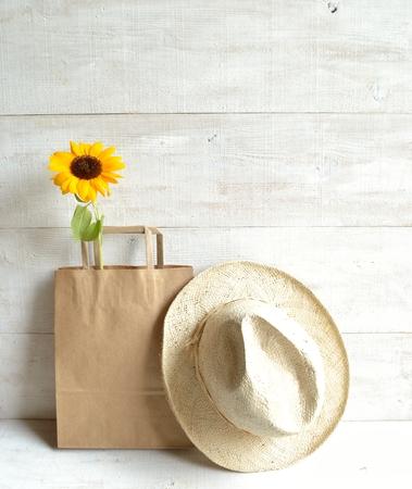sun s: Sacchetto di carta del mestiere, il cappello di paglia degli uomini con il fiore del sole Archivio Fotografico