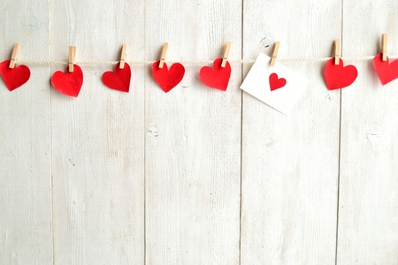 love: Red heart message card and red hearts with clothes pins