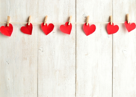 赤いハート紙を服のピンを切る