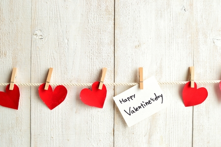 Valentines day message card and red heart with clothes pin