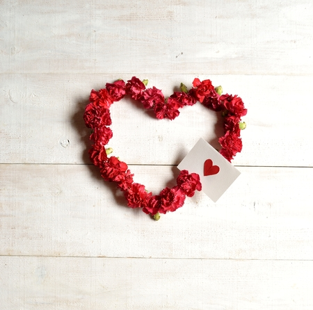 heart shaped: Red carnations heart shaped wreath with message card Stock Photo