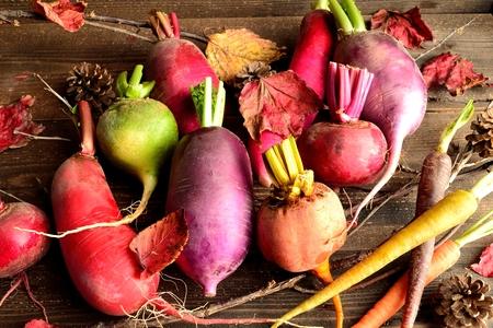 赤い落ち葉でカラフルな根菜