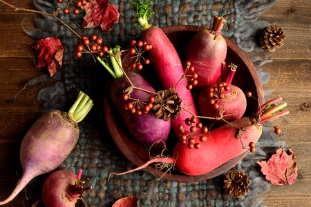 autumn food: Colorful root vegetables with fallen leaves on gray woolen fabric Stock Photo