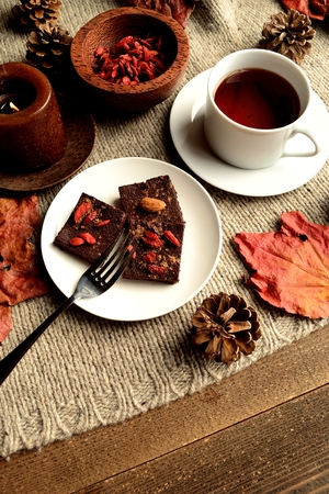 chocolate brownie: Raw chocolate brownie with gojiberries on the gray knitted fabric Stock Photo