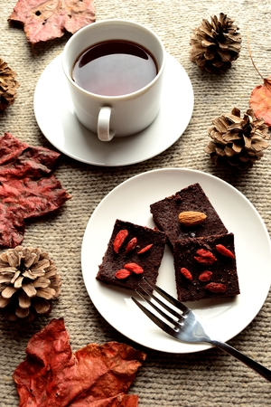 chocolate brownie: Raw chocolate brownie with red fallen leaves on the gray knitted fabric