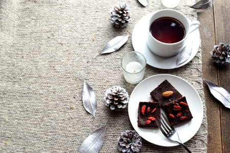chocolate brownie: Raw chocolate brownie with coffee cup on the gray knitted fabric