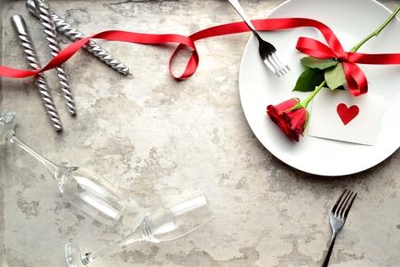 白い皿に赤いハートのメッセージ カードと赤いバラ