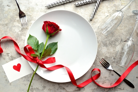 A single red rose on the white dish