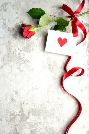 A single red rose with red heart message card