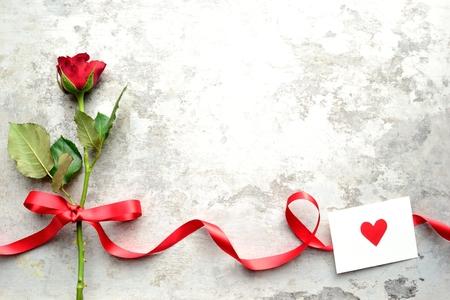 赤いハートのメッセージ カードで単一の赤いバラ 写真素材