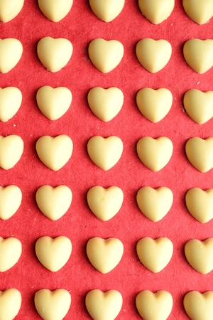 shaped: Heart shaped white chocolates on the red background