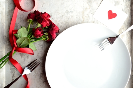 Red rose bouquet, red heart message card and white dish Stock Photo