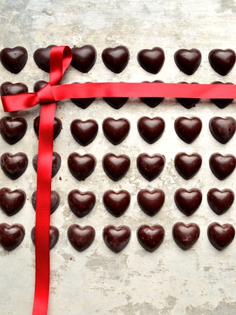 heart shaped: Heart shaped chocolates with red ribbon on the silver background
