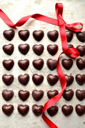shaped: Heart shaped chocolates with red ribbon on the silver background