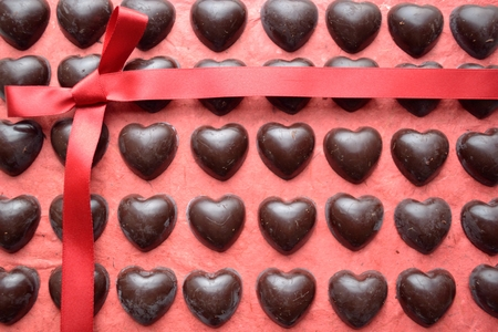 shaped: Heart shaped chocolates with ribbon on the red background Stock Photo