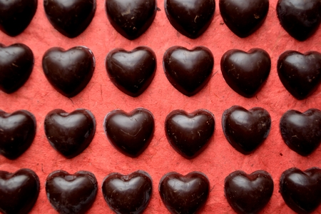 shaped: Heart shaped chocolates on the red background