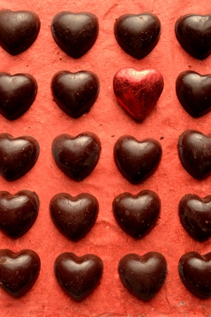heart shaped: Heart shaped chocolates with red heart on the red background Stock Photo