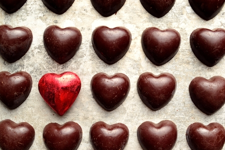 shaped: Heart shaped black chocolates with red heart Stock Photo