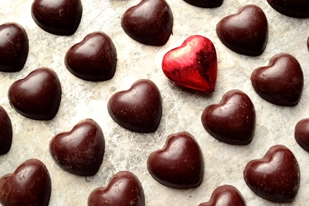 heart shaped: Heart shaped black chocolates with red heart Stock Photo