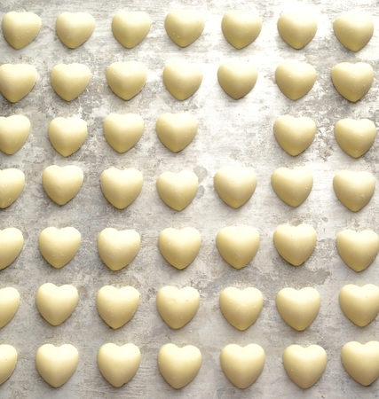shaped: Heart shaped white chocolates on the silver background
