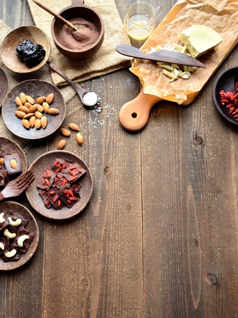 Raw chocolates, nuts and cutting board