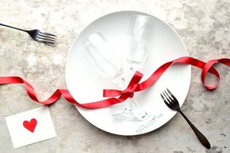Piatto bianco, un bicchierino di champagne, la message card e il nastro rosso Archivio Fotografico - 50857283