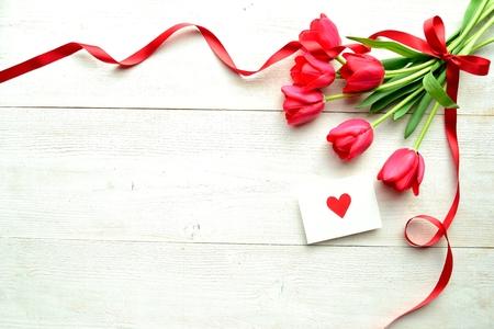 흰색 나무 배경에 붉은 마음 메시지 카드와 빨간 튤립 꽃다발