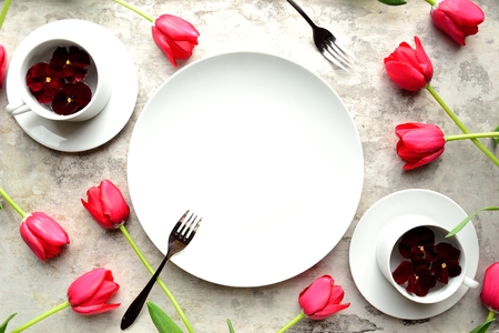 were: White dish were with red tulips on the silver background Stock Photo