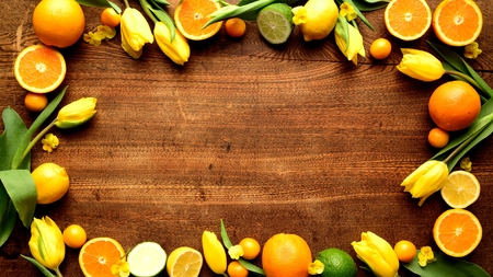 Citrus fruits with yellow tulips on the wooden background 版權商用圖片