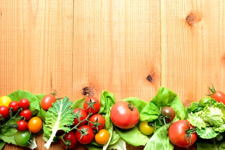 tomate ensalada: Colorful tomatoes with green leaves on the wooden background