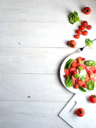 Tomatoes, cottage cheese and basil leaves salad with cutting board