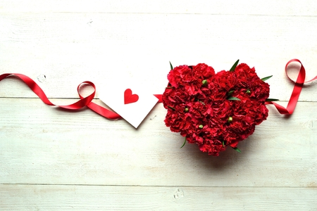 shaped: Heart shaped red carnations flower arrangement with message card Stock Photo